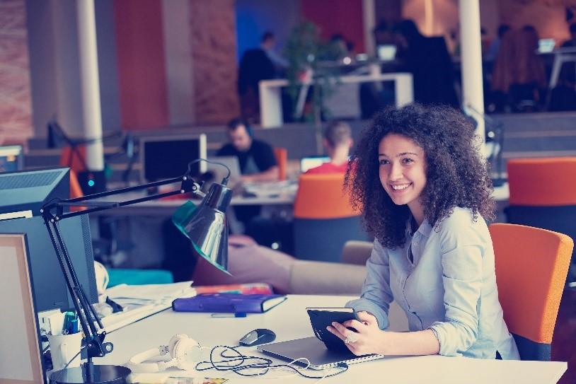 Mujer sentada en un escritorio  Descripción generada automáticamente