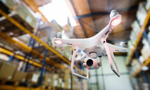 White drone flying inside the warehouse, under a wooden roof.